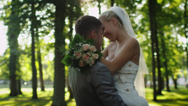 Bride-and-groom-hug-each-other-in-a-sunny-park-