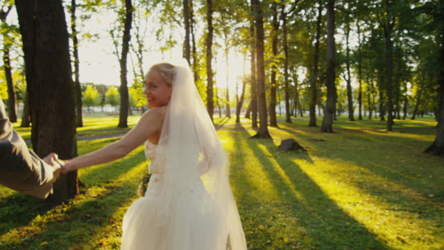 Smiling-bride-holds-groom-by-the-hand-and-runs-in-a-park-