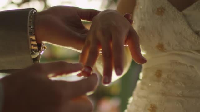 Novia-y-el-novio-intercambiar-anillos-de-boda-en-cerca-en-un-parque-