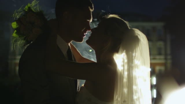 Happy-young-newlyweds-are-kissing-next-to-fireworks-in-a-park-in-the-evening-
