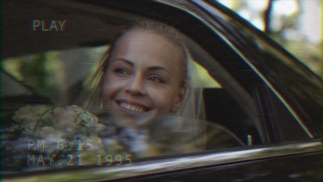 Young-beautiful-happy-bride-sits-in-a-car-and-waves-out-of-the-window-