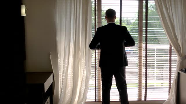 Man-in-suit-near-window-