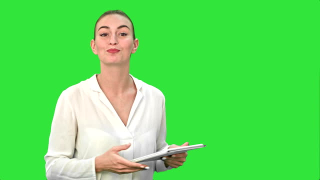 Young-women-standing-with-digital-tablet-presenting-the-project-on-a-Green-Screen-Chroma-Key