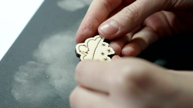 An-artist-looks-at-grinded-wooden-craft-on-sandpaper