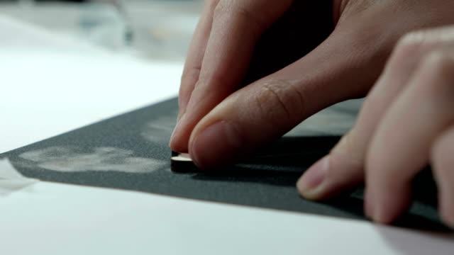 An-artist-grinds-wooden-craft-on-sandpaper