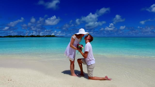v07387-Maldives-white-sandy-beach-2-people-young-couple-man-woman-proposal-engagement-wedding-marriage-on-sunny-tropical-paradise-island-with-aqua-blue-sky-sea-water-ocean-4k