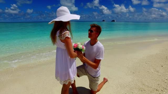 v07388-Malediven-weißen-Sandstrand-2-Menschen-junges-Paar-Mann-Frau-Vorschlag-Engagement-Hochzeit-Ehe-am-sonnigen-tropischen-Inselparadies-mit-Aqua-blau-Himmel-Meer-Wasser-Ozean-4k