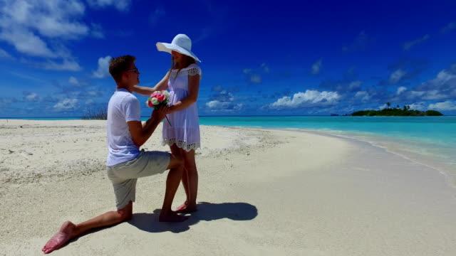 v07385-Malediven-weißen-Sandstrand-2-Menschen-junges-Paar-Mann-Frau-Vorschlag-Engagement-Hochzeit-Ehe-am-sonnigen-tropischen-Inselparadies-mit-Aqua-blau-Himmel-Meer-Wasser-Ozean-4k