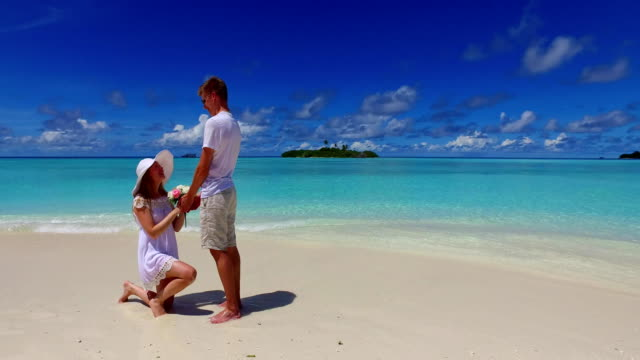v07390-Malediven-weißen-Sandstrand-2-Menschen-junges-Paar-Mann-Frau-Vorschlag-Engagement-Hochzeit-Ehe-am-sonnigen-tropischen-Inselparadies-mit-Aqua-blau-Himmel-Meer-Wasser-Ozean-4k