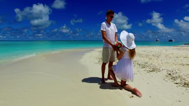 v07383-Malediven-weißen-Sandstrand-2-Menschen-junges-Paar-Mann-Frau-Vorschlag-Engagement-Hochzeit-Ehe-am-sonnigen-tropischen-Inselparadies-mit-Aqua-blau-Himmel-Meer-Wasser-Ozean-4k