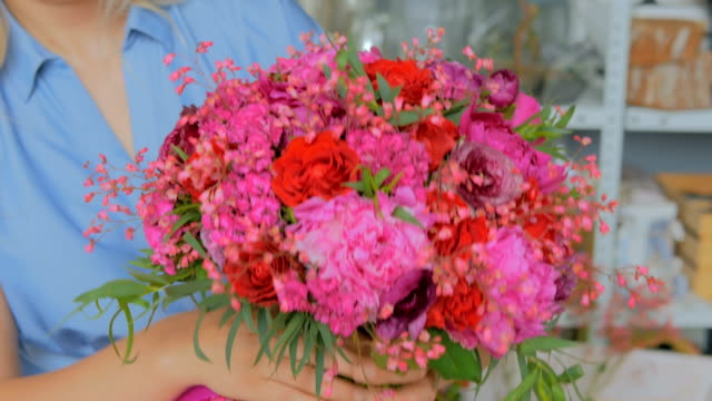 Professional-florist-holding-and-showing-bouquet-at-studio