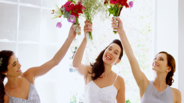 Bridesmaids-and-bride-having-fun-holding-flowers-in-the-air-4K-4k