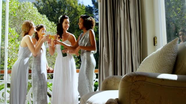 Novia-y-damas-de-honor-festejar-y-beber-champagne-de-vidrios-4K-4k
