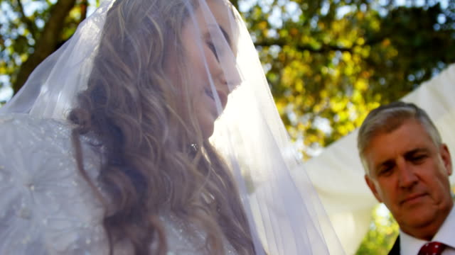 Bride-wearing-veil-and-priest-blessing-the-Bride-and-Groom-4K-4k
