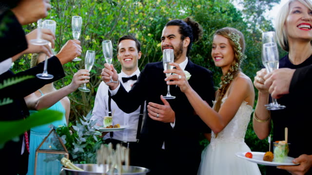 Guests-bride-and-groom-toasting-champagne-flutes-4K-4k