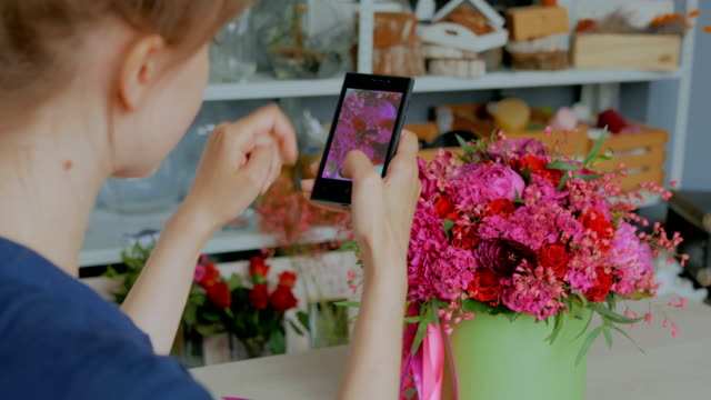 Woman-taking-photo-of-beautiful-bouquet-with-smartphone-