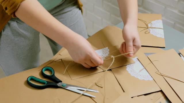 2-shots-Two-professional-women-decorators-making-envelopes-at-workshop
