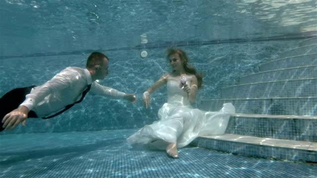 4K-el-novio-nada-bajo-el-agua-a-la-novia-que-se-encuentra-en-la-parte-inferior-de-la-piscina-y-besa-su-mano