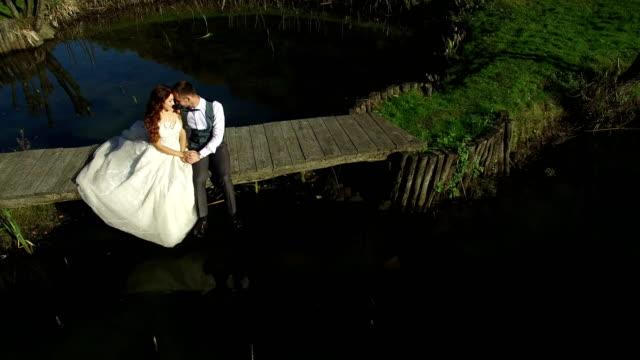 Las-novias-se-sientan-cerca-del-lago-en-un-pequeño-puente-en-el-Parque