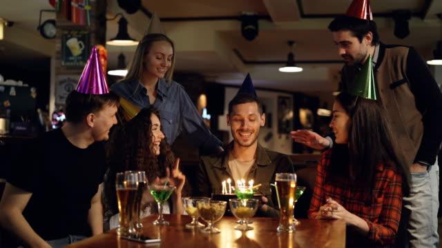 Atractivo-joven-es-lo-que-deseo-y-soplar-las-velas-sobre-el-pastel-y-celebrar-cumpleaños-en-bar-con-los-amigos-La-gente-feliz-son-felicitándole-y-palmas-de-las-manos-