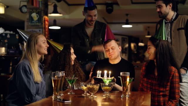 Mejores-amigos-están-felicitando-a-hombre-joven-en-cumpleaños-soplar-las-velas-sobre-el-pastel-y-agradeciendo-a-sus-compañeros-para-la-gran-fiesta-Vacaciones-divertidas-con-concepto-de-amigos-
