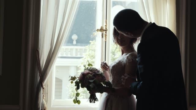 Heirat-mit-paar-umarmen-Sie-und-küssen-Sie-stehen-in-der-Nähe-von-riesigen-Fenster-im-Zimmer