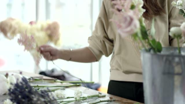 Young-Florist-Assembles-a-Rustic-Wedding-Bouquet