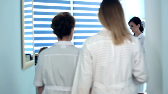 Doctors-reviewing-patient-folders-at-hospital-reception-desk