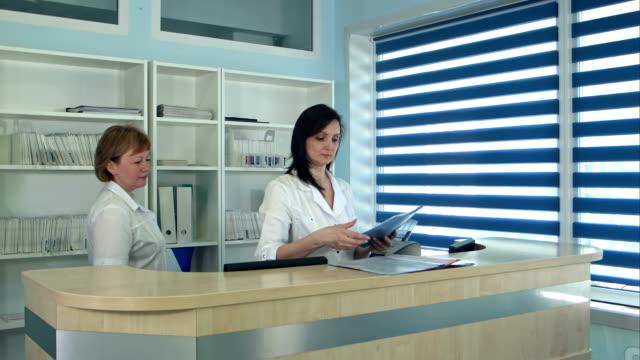 Lächelnde-Ärztinnen-stehen-an-der-Rezeption-im-Krankenhaus