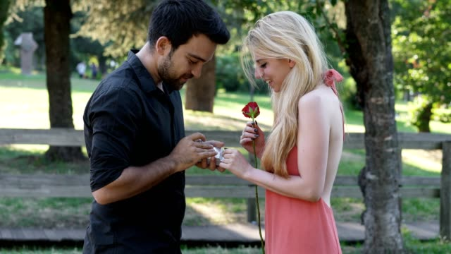 Proposal-of-marriage-at-the-park:-man-kneels-in-front-of-his-future-bride
