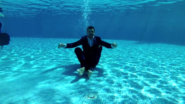 The-happy-groom-in-a-suit-and-a-white-shirt-goes-down-underwater-to-the-bottom-of-the-pool-He-sits-at-the-bottom-in-a-Lotus-position-looks-at-the-camera-and-smiles-Slow-motion-Action-camera-underwater-
