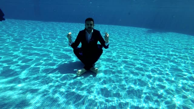 A-man-in-a-suit-and-a-white-shirt-meditates-under-the-water-in-the-pool-in-a-Lotus-position-He-sits-on-the-bottom-and-looks-around-Slow-motion-Action-camera-underwater-