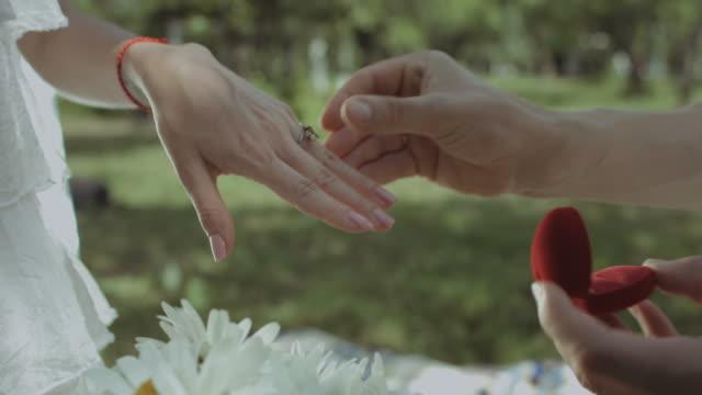 Hombre-poner-el-anillo-de-compromiso-en-mano-de-mujer-al-aire-libre
