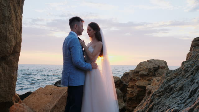 Beautiful-young-wedding-couple-standing-on-sea-shore-with-rocks-Newlyweds-spend-time-together:-embrace-kiss-and-care-for-each-other-Love-concept-Bride-smiling-to-groom
