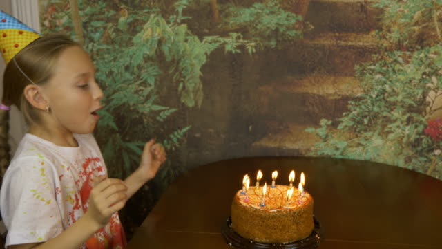 Funny-girl-can-not-blow-birthday-candles-on-cake-Joke-party-at-home-Young-girl-blowing-candles-on-cake-Lot-of-smoke-and-ash-on-table-Fast-motion-effect-Girl-clapping-