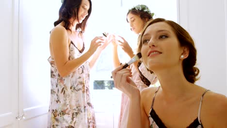 Bride-getting-ready-for-wedding-and-bridesmaids-with-head-wreath-in-background-4K-4k