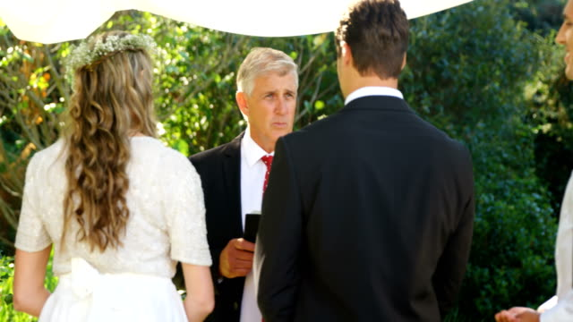 Priest-talking-to-the-bride-and-groom-4K-4k
