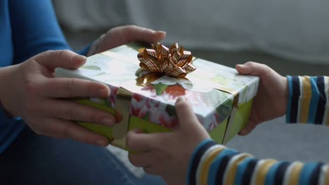 Child-hands-giving-holiday-gift-box-to-his-mother