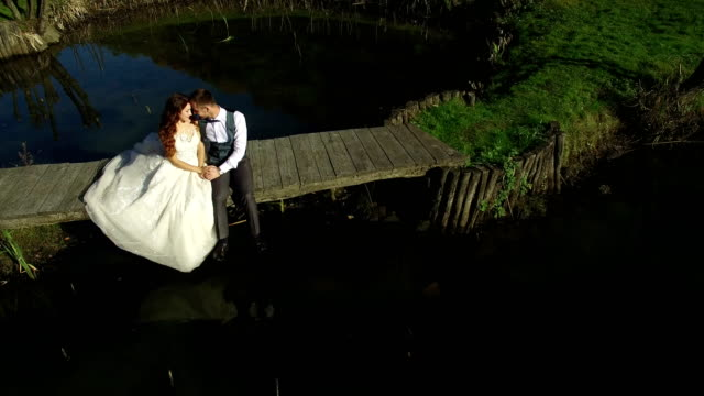 The-brides-sit-near-the-lake-on-a-small-bridge-in-the-park
