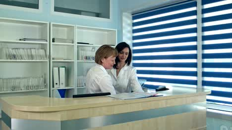 Smiling-female-doctors-standing-at-the-reception-desk-in-hospital