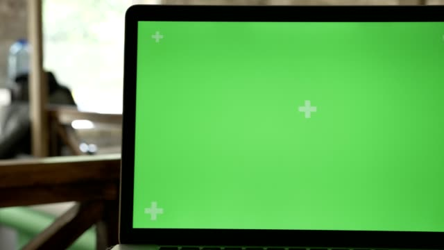 Close-moving-shot-of-laptop-display-with-chromakey-in-office-with-working-people