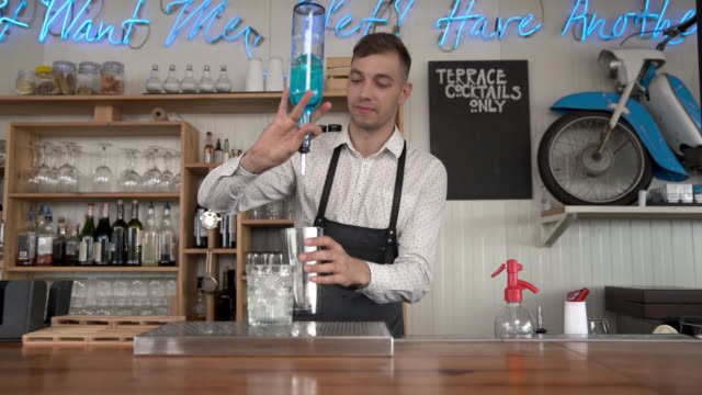 Funny-smiling-bartender-pours-a-blue-curacao-liquor-into-a-glass-with-ice-cubes-Flair-bartending-