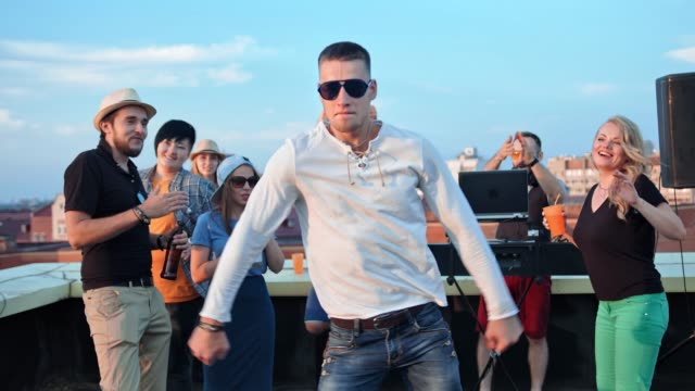 Active-European-man-in-sunglasses-having-fun-dancing-in-the-middle-of-dance-floor-at-rooftop-party