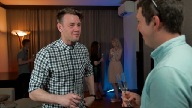 Attractive-guys-drinking-champagne-and-talking-at-birthday-party
