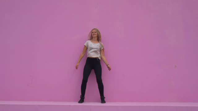 Casual-girl-with-braided-hair-having-fun-and-silly-dancing-over-pink-background