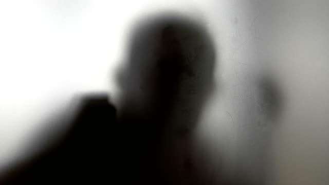 Hombre-bailando-detrás-de-vidrio-esmerilado-en-4-k-lenta-60fps