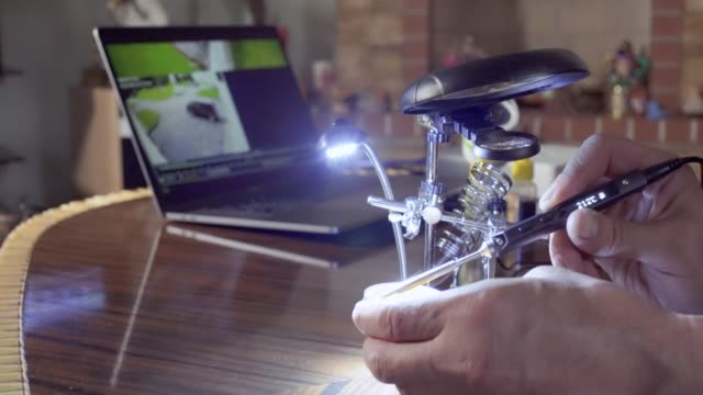 Hand-is-soldering-the-part-under-the-magnifying-glass-