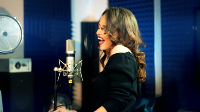 Girl-singing-to-the-microphone-in-a-studio-