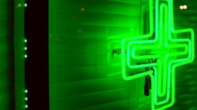 panning-of-marijuana-dispensary-neon-green-weed-cross-on-city-store-front-window