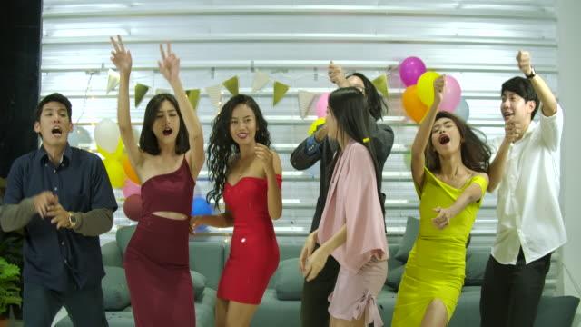 Grupo-de-jóvenes-amigos-bailando-juntos-en-una-fiesta-las-personas-con-el-concepto-de-fiesta-celebración-disfrute-y-año-nuevo-Cámara-lenta-